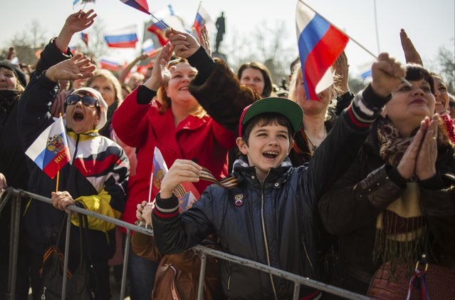 In this Tuesday, March 18, 2014 file photo people wave Russian flags as they gather at a square to watch a televised address by Russian President Vladimir Putin to the Federation Council, in Sevastopol, Crimea. (Photo by Andrew Lubimov/AP Photo)