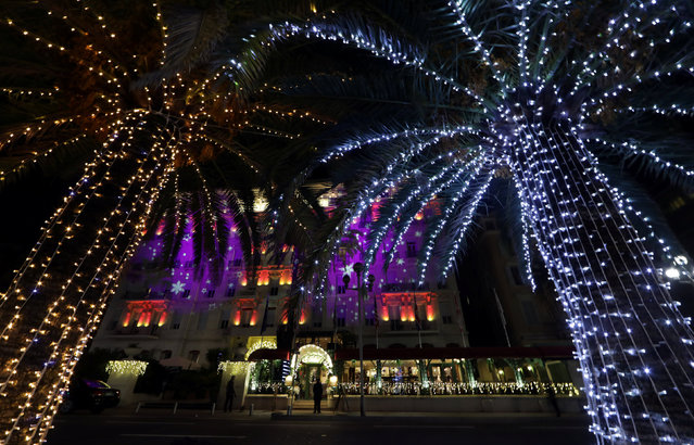 Colored lights are seen on palm trees and hotels on the Promenade Des Anglais as part of illuminations for the Christmas holiday season in Nice, France, December 13, 2016. (Photo by Eric Gaillard/Reuters)