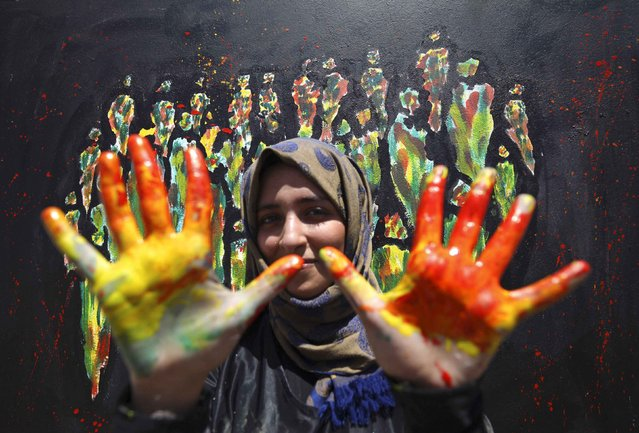 An artist shows her hands after working on a wall as part of a campaign to call for coexistence and the renouncement of violence through the painting of walls in Sanaa, Yemen March 15, 2015. (Photo by Mohamed al-Sayaghi/Reuters)