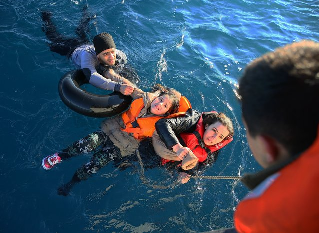 Turkish Coast Guard personnel help refugees as they swim with buoys, after they toppled over a fishermen dinghy en route to Greece on January 22, 2016 in Didim district of  Aydin, Turkey. 4 refugees body including 3 children pulled out of the water as Turkish coast guard personnel rescued 43 others. (Photo by Emin Menguarslan/Anadolu Agency/Getty Images)