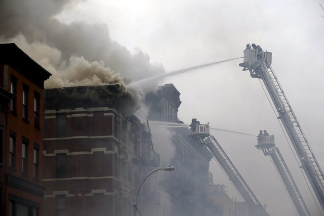 New York City Fire Department firefighters battle fire at the site of a residential apartment building in New York City's East Village neighborhood March 26, 2015. (Photo by Mike Segar/Reuters)