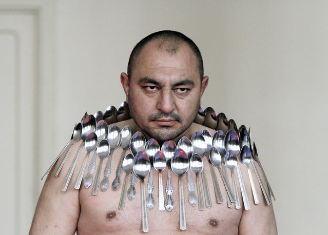 """Etibar Elchiyev poses with 50 metal spoons magnetized to his body during an attempt to break the Guinness World Record for """"Most spoons on a human body"""" in Tbilisi December 14, 2011. (Photo by David Mdzinarishvili/Reuters)"""