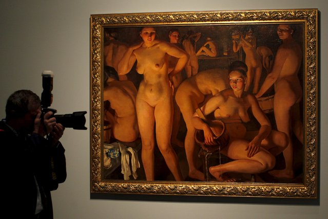 """A man takes pictures next to """"Bath-House"""" by Russian-born artist Zinaida Serebryakova during an international press tour of the Malaga branch of the State Museum of Russian Art of St Petersburg, a day before its inauguration in Malaga, southern Spain March 24, 2015. Malaga's branch is the first branch outside Russia and is located in the Tabacalera building, a former tobacco factory. (Photo by Jon Nazca/Reuters)"""