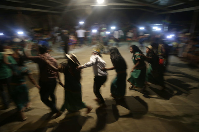 In this November 25, 2018 photo, Ngabe Bugle indigenous people dance during the opening of the second edition of the Panamanian indigenous games in Piriati, Panama. At night, the groups intermingled to share dance and music traditions. (Photo by Arnulfo Franco/AP Photo)