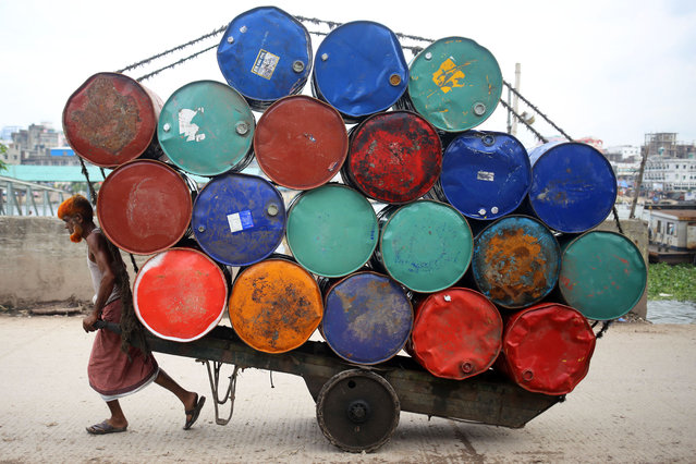 A laborer is transporting used oil durms by a hand-pulled vehicle near Buriganga River in Dhaka on June 12, 2021. (Photo by Md Rakibul Hasan/ZUMA Wire/Rex Features/Shutterstock)