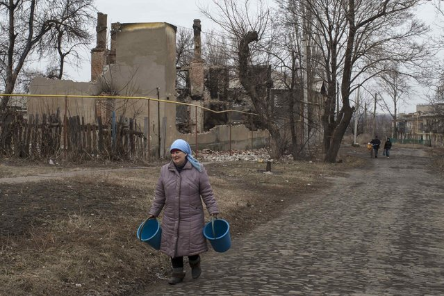 A woman walks along a street in the village of Chornukhyne near the town of Debaltseve, north-east from Donetsk, March 12, 2015. (Photo by Marko Djurica/Reuters)