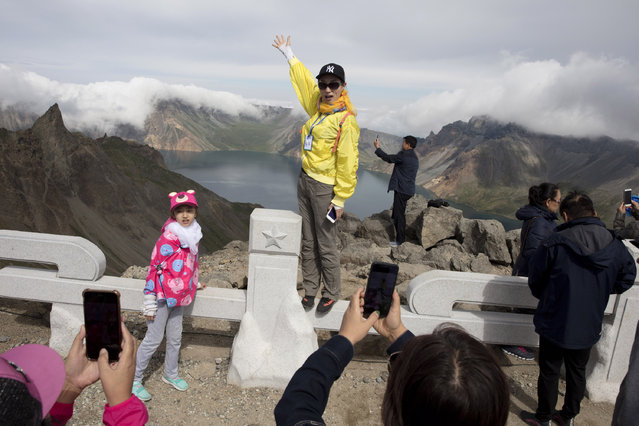 In this August 18, 2018, file photo, Chinese tourists pose for photos overlooking the caldera of Mount Paektu in North Korea. There is no more sacred a place in North Korea than Mount Paektu. The still active volcano, site of one the most violent eruptions in history, is considered to be the spiritual epicenter of the North Korean revolution. (Photo by Ng Han Guan/AP Photo)