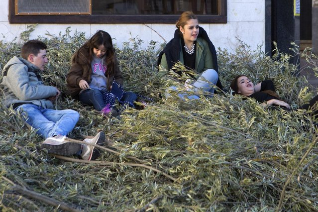 Youths sit of a pile of tree branches to be burned with a cross being erected in the village square in Tielmes, Spain on Easter Sunday  Sunday, April 5, 2015 marking the end of Holy week. (Photo by Paul White/AP Photo)