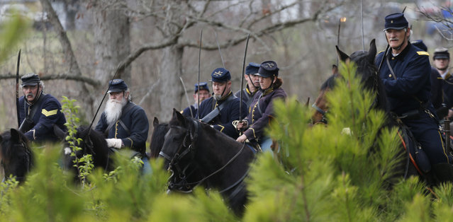 Union cavalry wait in the woods as they prepare to charge during a re-enactment of the Battle of Appomattox Station, Wednesday, April 8, 2015, as part of the 150th anniversary of the surrender of the Army of Northern Virginia to Union forces at Appomattox Court House, in Appomattox, Va. (Photo by Steve Helber/AP Photo)