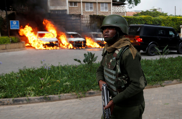 A member of security forces walks as cars are seen on fire at the scene where explosions and gunshots were heard at the Dusit hotel compound, in Nairobi, Kenya on January 15, 2019. (Photo by Baz Ratner/Reuters)