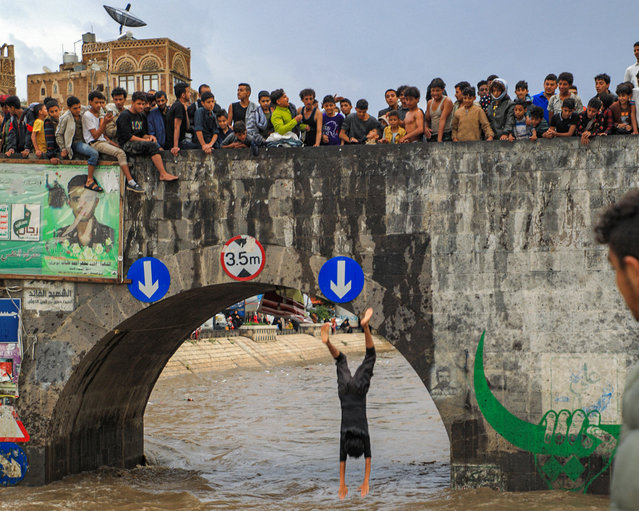 Youths watch as one jumps from a bridge across a flooded drainage canal following heavy rainfall in the old city of Yemen's capital Sanaa on August 3, 2021. (Photo by Mohammed Huwais/AFP Photo)