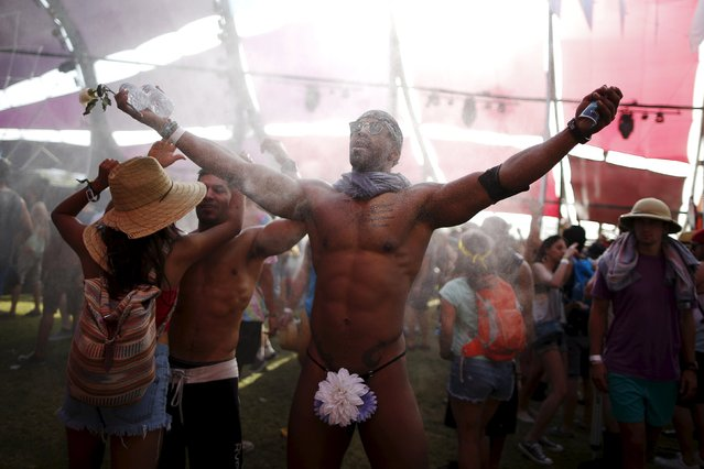 Cameron Pugh, 24, from Fresno, dances in the mist at the Coachella Valley Music and Arts Festival in Indio, California April 10, 2015. (Photo by Lucy Nicholson/Reuters)