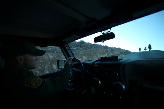 U.S. Border Patrol supervisor Bobby Stine drives a car as he catches up with his horse patrol near Jacumba, California, U.S., November 14, 2016. (Photo by Mike Blake/Reuters)