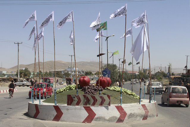 Taliban flags fly at a square in the city of Ghazni, southwest of Kabul, Afghanistan, Saturday, August 14, 2021. (Photo by Gulabuddin Amiri/AP Photo)