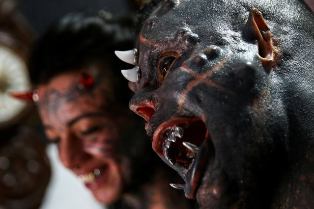 Brazilian tattoo artist Michel Praddo, also known as Diabao or Human Satan, and his wife Carol Praddo, known as Mulher Demonia or Demon Woman, pose in their studio in Praia Grande, Brazil on August 18, 2021. Prado, known on social media as Diabao Praddo or Devil Praddo, changed his appearance by tattooing 80% of his body, reducing his nose size and removing one of his ring fingers to mimic a claw-like hand. He also has sharpened fangs and implanted horns. (Photo by Carla Carniel/Reuters)
