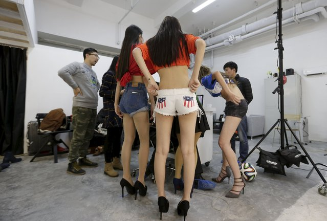 Online hostess Xianggong (L) and other hostesses check their pictures as they gather around the photographer while taking part in a football-themed photoshoot at a photography studio in Beijing March 4, 2015. (Photo by Jason Lee/Reuters)