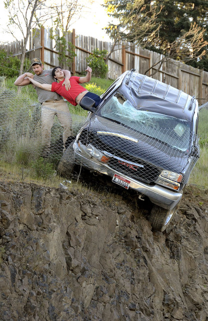 An unidentified passer-by pulls the driver from a SUV to safety after the vehicle left Mayfair Drive, traveled downhill and was stopped by a chain link fence just short of a 30-foot vertical drop onto the Bryden Canyon Road, Wednesday, April 15, 2015, in Lewiston, Idaho. (Photo by Barry Kough/Lewiston Tribune via AP Photo)