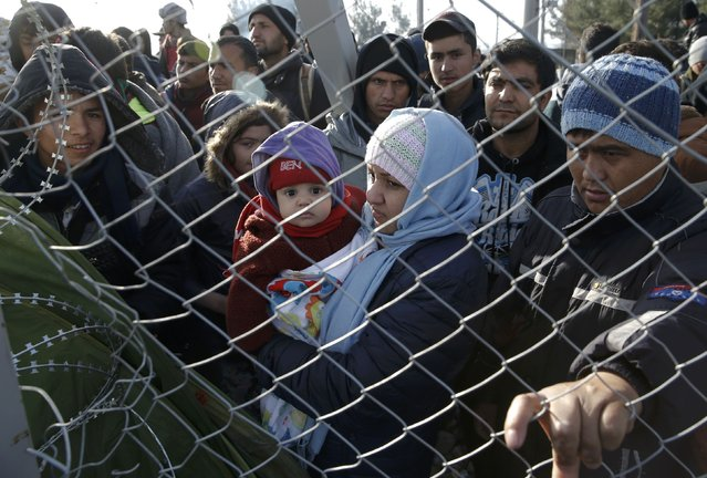 Migrants stand next to a border fence at the Greek-Macedonian border, after additional passage restrictions imposed by Macedonian authorities left hundreds of them stranded near the village of Idomeni, Greece, February 23, 2016. The picture was taken from the Macedonian side of the border. (Photo by Marko Djurica/Reuters)