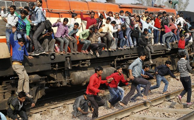 Passengers jump from an overcrowded train near a railway station at Loni town in the northern state of Uttar Pradesh, India, February 24, 2016. (Photo by Anindito Mukherjee/Reuters)