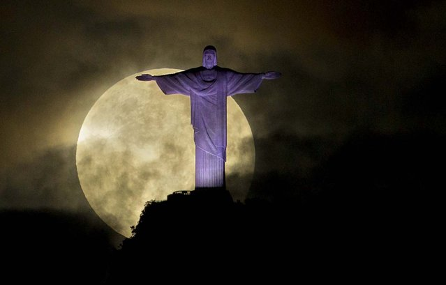 "A ""supermoon"" is seen behind the Christ the Redeemer statue on May 6, 2012. (Photo by Victor R. Caivano/Associated Press)"