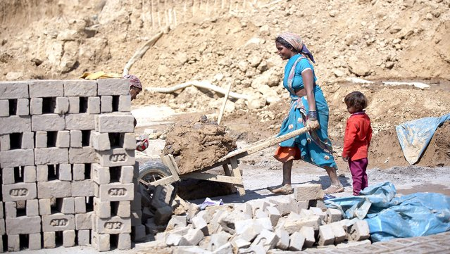 An Indian woman works at a brick factory on International Women's Day, on the outskirts of Jammu, the winter capital of Kashmir, India, 08 March 2016. International Women's Day is globally observed on 08 March, in order to highlight the struggles of women across the globe and promote women's rights. (Photo by Jaipal Singh/EPA)