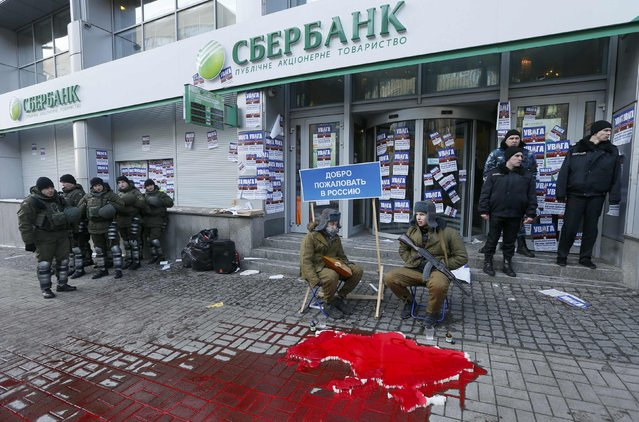 """Members of the Azov civil corp sit next to a placard reading, """"Welcome back to Russia"""" during a protest in front of a branch of Sberbank, which they say supports Russian """"aggression"""" in Eastern Ukraine, in Kiev, Ukraine January 30, 2017. (Photo by Valentyn Ogirenko/Reuters)"""