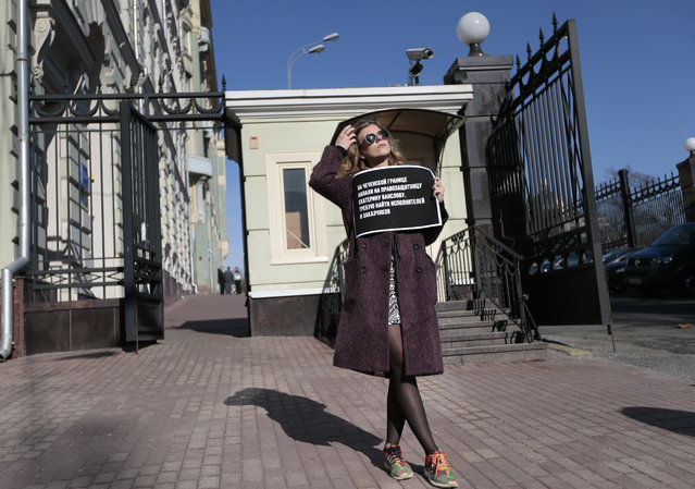 A human rights activist holds a poster as she pickets Russian President's Administration building in Moscow, Russia on Thursday, March 10. 2016. The Committee to Protect Journalists is blaming Russian authorities' inattention to anti-media hostility as enabling the attack near Chechnya that left six journalists injured. The CPJ's statement Thursday came a day after attackers intercepted a small bus carrying activists and journalists, beat them and set the vehicle afire. (Photo by Ivan Sekretarev/AP Photo)