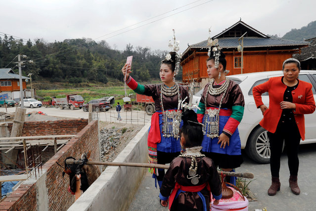 "Ethnic ""Kam"" (also known as Dong) women take a selfie before a traditional wedding ritual ""steal the chicken at the drum tower"" in a minority Dong village in southwestern Chinese city of Congjiang, Guizhou province, China January 29, 2017. (Photo by Tyrone Siu/Reuters)"