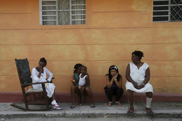 People wait on the sidewalk while military reservists fumigate their home against mosquito breeding to prevent diseases such as malaria, dengue and Zika, during a fumigation campaign in Havana, February 22, 2016. (Photo by Reuters/Stringer)