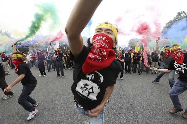"People throw smoke grenades during the annual Labour Day protest in front of Presidential Office in Taipei, Taiwan, May 1, 2015. Thousands of people marched to demand higher wages and labour rights, according to local media. The head banner reads, ""shorten working hours; no overfatigue"". (Photo by Patrick Lin/Reuters)"