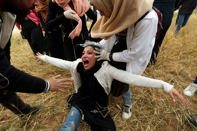 A Palestinian woman reacts after inhaling tear gas fired by Israeli forces during a protest marking Land Day and the first anniversary of a surge of border protests, at the Israel-Gaza border fence, in the southern Gaza Strip March 30, 2019. (Photo by Ashraf Abu Amrah/Reuters)
