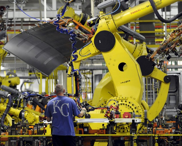 An auto worker feeds aluminum panels to robots at Ford's Kansas City Assembly Plant where new aluminum intensive Ford F-Series pickups are built in Claycomo, Missouri May 5, 2015. (Photo by Dave Kaup/Reuters)