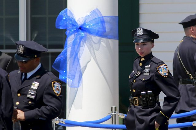 NYPD police officers stand outside the wake of officer Brian Moore at the Fredrick J. Chapey and Sons Funeral Home in Bethpage, New York, May 7, 2015. (Photo by Shannon Stapleton/Reuters)