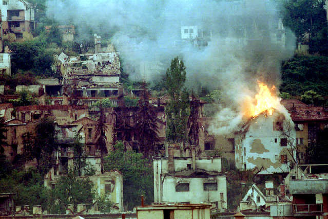 A house is burning down near the Jewish cemetery in Sarajevo, 1994. The house caught fire following a mortar explosion. (Photo by Peter Andrews/Reuters)