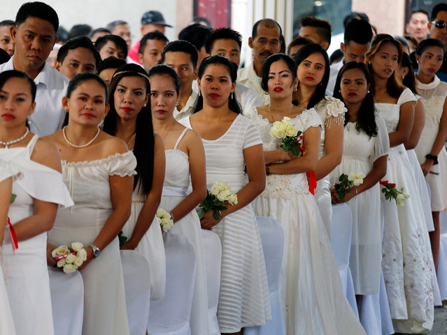 A crowd of Filipino couple exchange vows during a mass wedding on Valentine's Day in the fishing municipality of Noveleta, Cavite province, Philippines, 14 February 2107. At least a hundred Filipino couples participated in a civil mass wedding officiated by Novelata Mayor Dino Reyes Chua to strengthen family ties. (Photo by Francis R. Malasig/EPA)