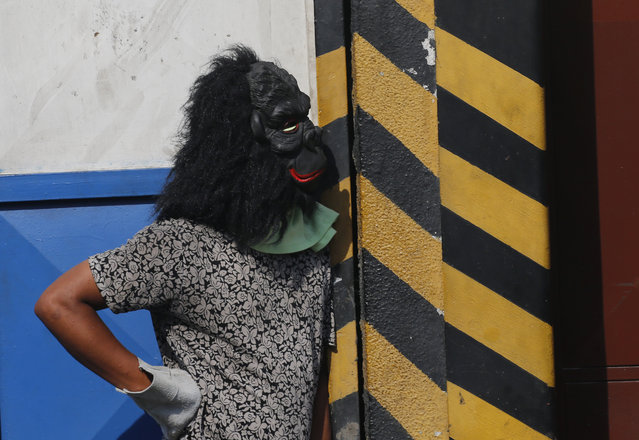An anti-government protester, wearing a gorilla mask, keeps an eye on the movement of security forces during clashes between the two, in Caracas, Venezuela, Wednesday, May 1, 2019. (Photo by Fernando Llano/AP Photo)