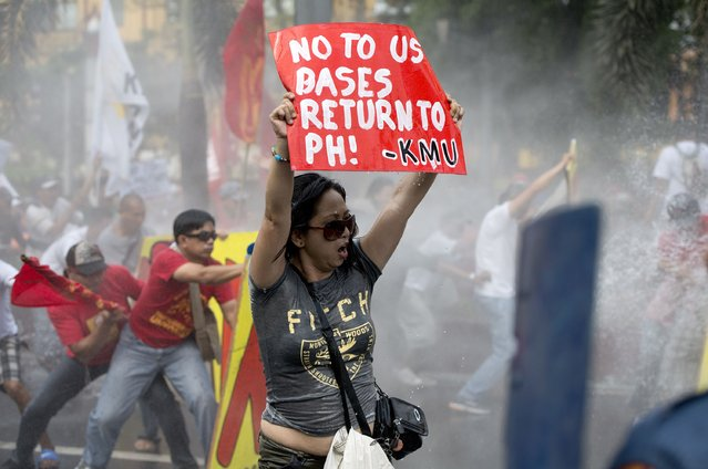 Protesters brace themselves as policemen use a water cannon during a protest in front of the US embassy in Manila on February 25, 2014. Protesters called for an end to what they described as US meddling in Philippine sovereignty, and against the expected visit of US President Barack Obama in April. (Photo by Noel Celis/AFP Photo)