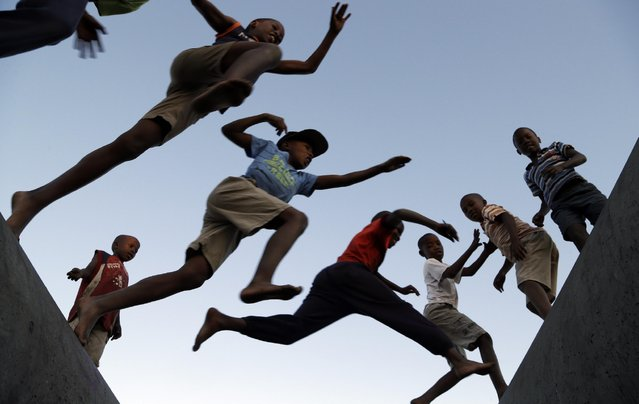 Young boys jumps from one concrete drainage pipe to another in a park in Katlehong, south of Johannesburg, South Africa, Wednesday, May 6, 2015. (Photo by Themba Hadebe/AP Photo)