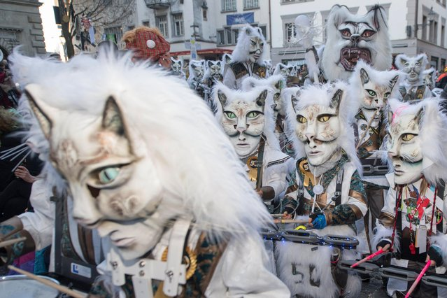 Masked Guggen music bands (brass and percussion carnival bands) parade through the streets at the beginning of the Lucerne Carnival in Lucerne, Switzerland, 23 February 2017. (Photo by Urs Flueeler/EPA)