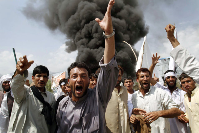 Afghans shout anti-U.S. slogans as they burn tires and block a highway during a protest in reaction to a small American church's plan to burn copies of the Quran, at Jalalabad, east of Kabul, Afghanistan, Friday, September 10, 2010. Religious and political leaders across the Muslim world welcomed a decision by the church to suspend its plans to torch copies of their holy book but some said Friday the damage has already been done. (Photo by Rahmat Gul/AP Photo)