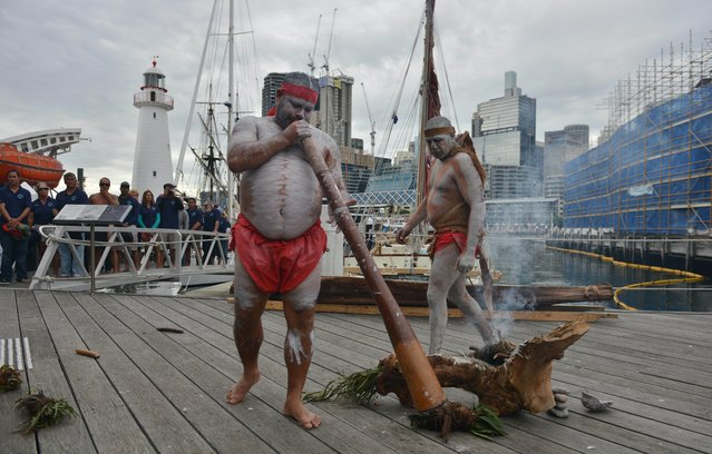Australian aboriginal elders perform a smoking ceremony to welcome members of the Polynesian Voyaging Society on the voyaging canoe Hōkūleʻa on its 47,000 nautical mile journey over four years to engage a global community in creating a healthy and sustainable planet in Sydney on May 19, 2015. (Photo by Peter Parks/AFP Photo)