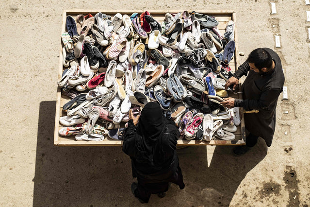 A customer buys shoes from a street vendor in the northern Syrian city of Raqa, the former Syrian capital of the Islamic State (IS) group, on April 14, 2019. The Kurdish-led Syrian Democratic Forces overran Raqa in 2017, after years of what residents described as IS's brutal rule, which included public beheading and crucifixions. (Photo by Delil Souleiman/AFP Photo)