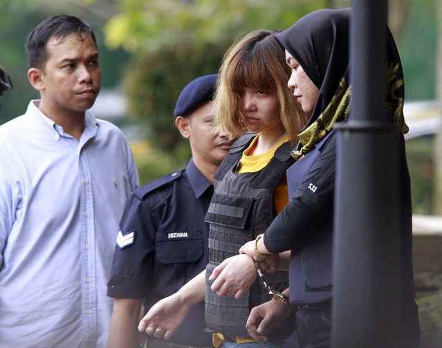 Vietnamese national Doan Thi Huong (L), 28, is escorted with a heavy police presence after a court appearance with Indonesian national Siti Aisyah, 25, at the magistrates' court in Sepang on March 1, 2017, for their alleged role in the assassination of Kim Jong- Nam, the half- brother of North Korean leader Kim Jong- Un Two women were charged March 1 with the murder of Kim Jong- Nam, the half- brother of North Korea' s leader, after his assassination at a Malaysian airport last month. (Photo by Daniel Chan/AP Photo)