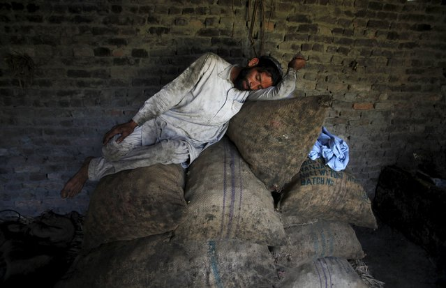 A laborer sleeps on sacks of charcoal in his workplace in Charsadda near Peshawar April 8, 2015. (Photo by Fayaz Aziz/Reuters)