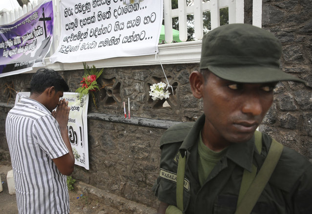 """A relative of an Easter Sunday bomb blast victim prays after placing the flowers on the wall of St. Sebastian's Church in Negombo, north of Colombo, Sri Lanka, Sunday, April 28, 2019. Sri Lanka's Catholics celebrated Sunday Mass in their homes by a televised broadcast as churches across the island nation shut over fears of militant attacks, a week after the Islamic State-claimed Easter suicide bombings killed over 250 people. Banner in Sinhalese reads, """"those innocents who went to church in the break of the day with thousands of expectations had to depart to the almighty"""". (Photo by Manish Swarup/AP Photo)"""