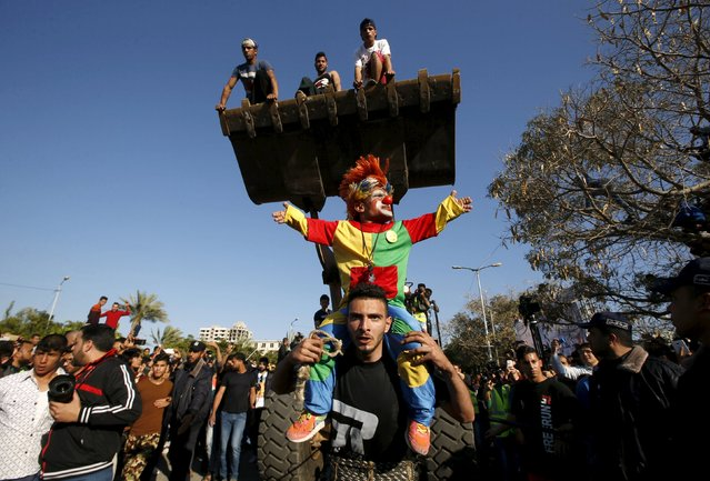 Palestinian Mohammad Baraka, nicknamed Gaza Samson, pulls a bulldozer by a rope tried around his waist as he holds a man dressed as a clown during a cultural carnival organized by Gaza Municipality in Gaza City April 1, 2016. (Photo by Mohammed Salem/Reuters)