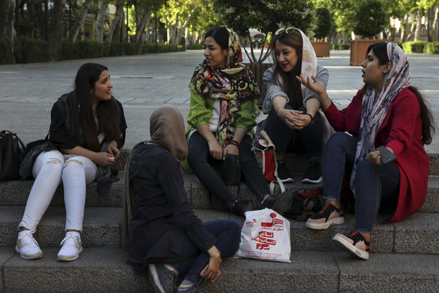 In this Saturday, May 18, 2019 photo, a group of students spend time together after classes in downtown Tehran, Iran. (Photo by Vahid Salemi/AP Photo)