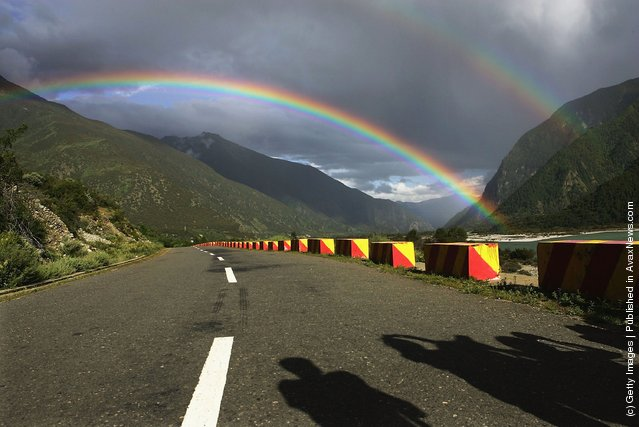 Tourists take pictures of a rainbow at a highway in Nyingchi County of Lhasa