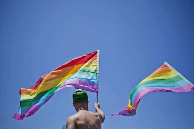 A man waves a rainbow flag during the annual Gay Pride Parade in Tel Aviv, Israel, Friday, June 12, 2015. Thousands of bare-chested muscular men, drag queens in heavy makeup and high heels, women in colorful balloon costumes and others partied at Tel Aviv's annual gay pride parade on Friday, the largest event of its kind in the region. (AP Photo/Ariel Schalit)