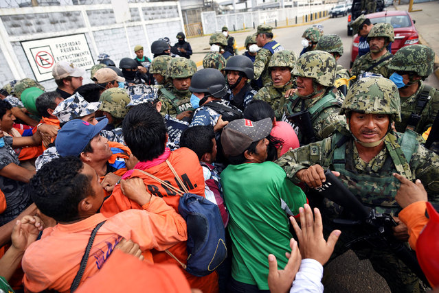 Relatives of injured or missing workers scuffle with Mexican marines blocking the access to Mexican national oil company Pemex's Pajaritos petrochemical complex in Coatzacoalcos, Veracruz state, Mexico, April 21, 2016. (Photo by Angel Hernandez/Reuters)